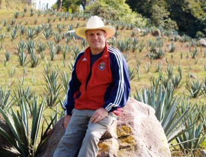 Craig Reynolds sitting amidst his field of young Agave plants